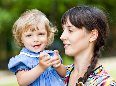 Little girl with her mom outdoors - shallow DOF photo