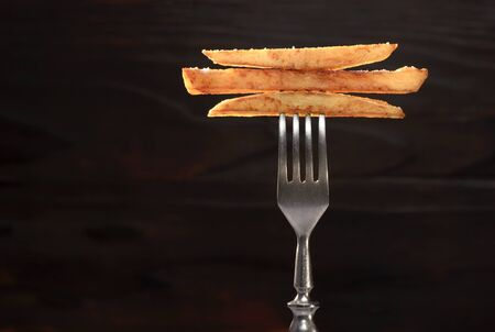 French fry on a folk with dark wooden background. Macro photo.