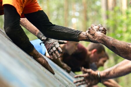Folks help each other during mud racing on an obstacle course. Selective focus.