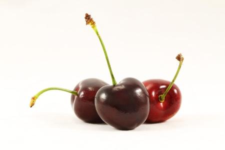 bing: Macro of three firm ripe black cherries macro on white background Stock Photo