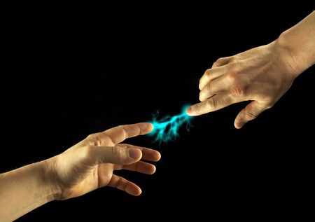Sparks between fingertips of two people