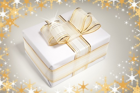 giftboxes: White gift box with bow ribbon. Snowflakes background