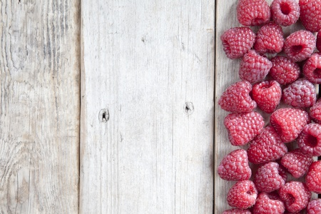 Fresh raspberries scattering on a wooden background photo