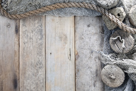 Cork, fishing net and rope with wooden background