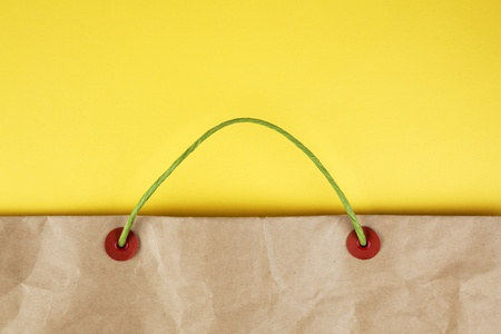 reusable: Paper bag with handles on yellow background Stock Photo