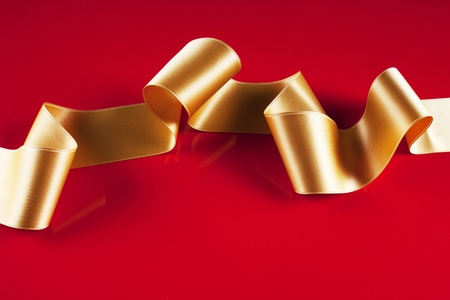 silk bow: Gold ribbon banner on red background Stock Photo