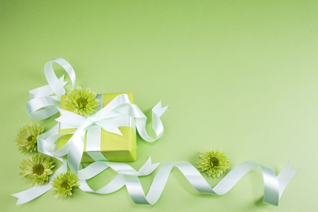 Gift box with flowers on green background  photo