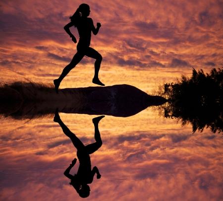 Female runner silhouette against the sunset  Stock Photo