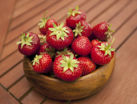 Fresh strawberries in wood bowl on table photo