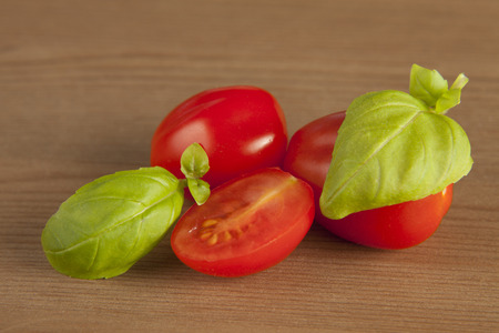 Cherry tomatoes and basil on wooden background