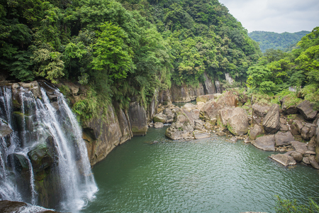 Shifen Waterfall is a scenic waterfall located in Pingxi District, New Taipei City, Taiwan, on the upper reaches of the Keelung River. Stock Photo