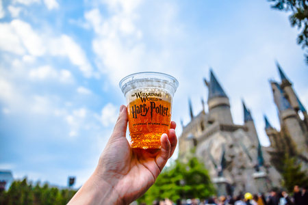 Osaka, Japan - November 17, 2018: Hand holding cup of Butter beer in Wizarding World at Universal Studios Japan.