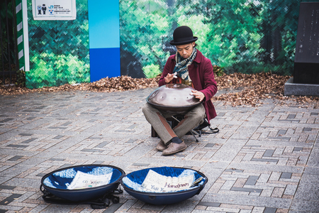 Tokyo, Japan - December 2, 2018: A Japanese street music performer playing some unique music with a handcrafted musical instrument called handpan.