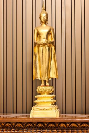 A stand Golden Budha hold an alms bowl