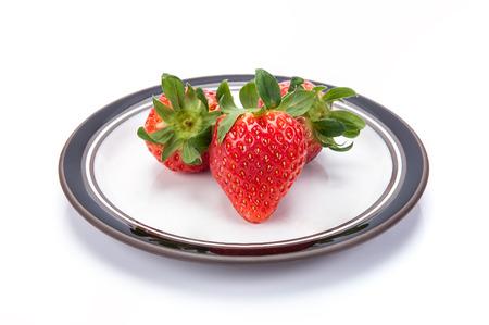 sepals: fresh garden strawberries on a white plate