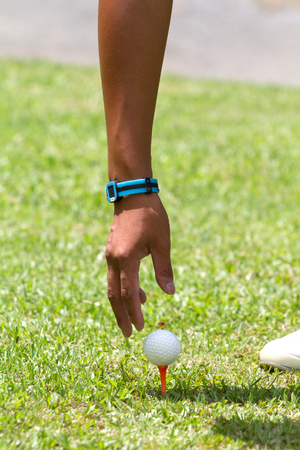 tee off: man golf player pick ball at tee off