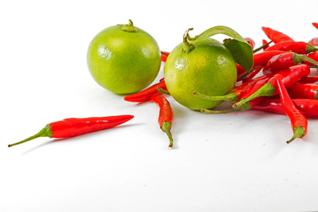 spur: red chili spur pepper and green lemon on white background Stock Photo
