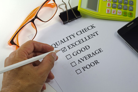 quality check: hand holding pencil check on quality check paper mark on excellent with eyeglasses calculator clip and mobile phone