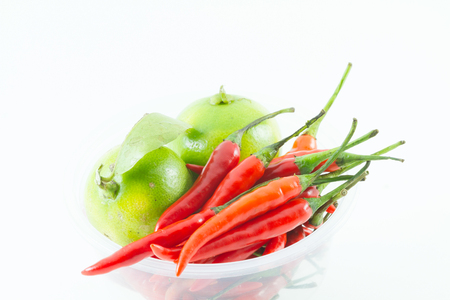 red chili spur pepper and green lemon on white background Stock Photo