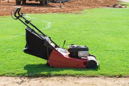 red mower ready to work on green grass lawn under sunlight Imagens