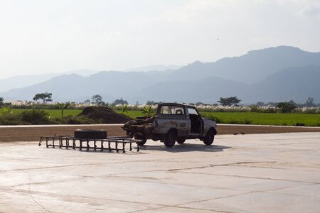 Pickup truck and rake use for spread rice on the concrete floor to drying in sunlight a after harvest before taking it to the milling station for processing or store, in Thailand