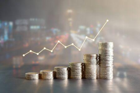 Pile à double exposition de pièces de monnaie thaïlandaises sur une table en bois noire avec graphique de profit, croissance, succès sur fond flou de la route de nuit. Affaires, finance, marketing, concept et design de commerce électronique