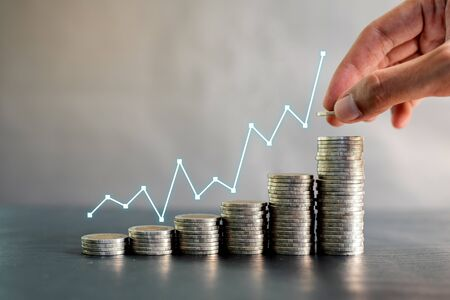 Hand stacking coins on black wooden table with profit line chart growth up. Business, finance, marketing, e-commerce concept and design