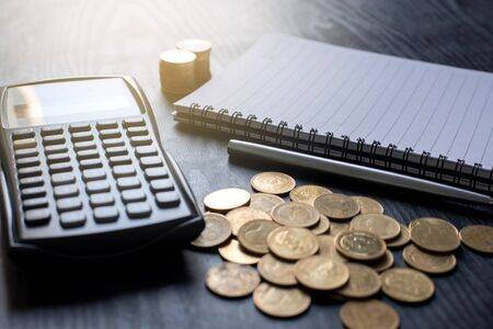 Close up gold coins, calculator, pen, notebook on black table. Business, finance, marketing, e-commerce concept and design
