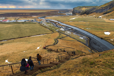 SKOGAFOSS, ICELAND - DECEMBER 30, 2015 : Travelers climb up steps to see this view point from above, you also can walk right up the river. Fantastic and a quick visit just a 5 min walk to the falls. Editorial