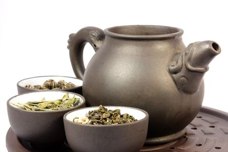 Teapot and three bowls of herbal tea. Close-up, isolated on white.