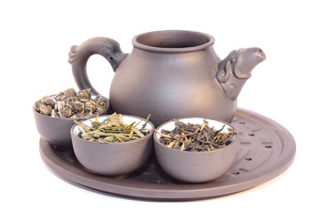 Teapot and three cups of herbal tea. Close-up, isolated on white.