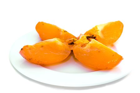 Persimmon on white plate. Isolated. Stock Photo