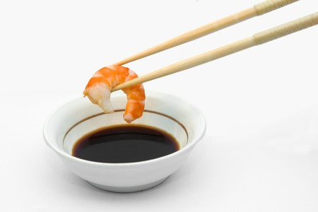Shrimp in chopsticks and soy sauce.