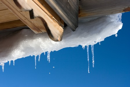 Wooden roof and icicles. Winter. Stock Photo