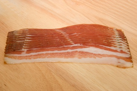 Raw bacon slices on wooden table.