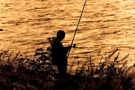 日没の漁師のシルエット。 写真素材