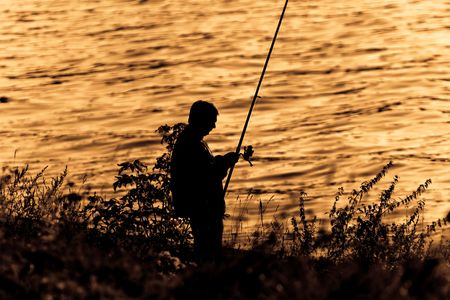 Silhouette of Fisherman on sunset.