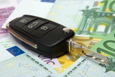 お金の背景上の車のキー。
