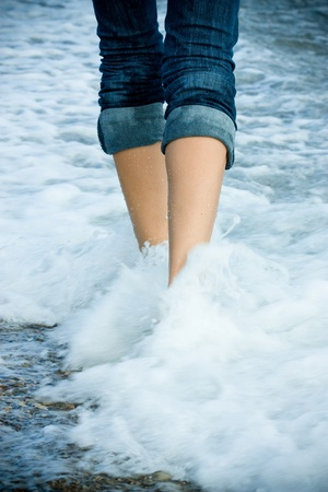 wet jeans: Legs of a young woman walking along the seacoast