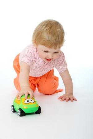 juguetes antiguos: Retrato de estudio de la beb� de 1 a�o de edad jugando con un coche de juguete en el fondo blanco