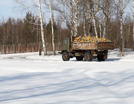 Truck transporting firewoods along the snow-covered road Stock Photo