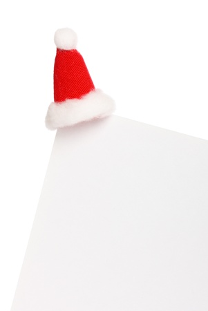 Clear sheet of paper with Santas cap isolated on white  photo