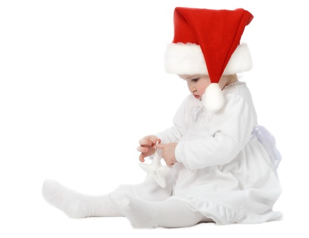 sincere girl: Funny baby girl examining New Year toy Stock Photo