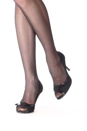 Close-up of young woman�s legs in high-heeled black shoes isolated on white photo