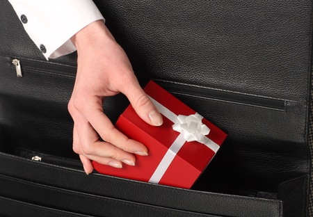 A hand pulling Christmas present in a red box from a black bag Stock Photo - 10867497