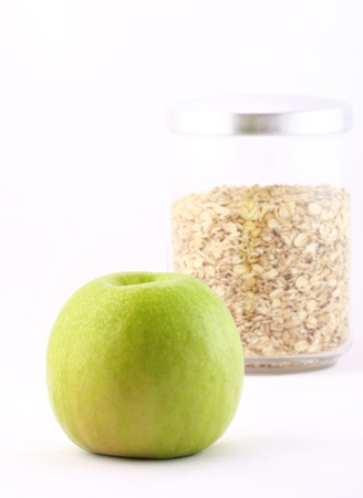 nourishment: Healthy nourishment: oat flakes and green apple isolated on white