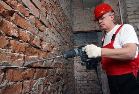 casco rojo: Casa-constructor en el casco de color rojo uniforme y trabajar con un condensador contra la pared de ladrillo Foto de archivo