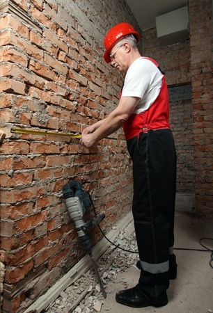 tapeline: House-builder in uniform with a tape-line against the brick wall Stock Photo