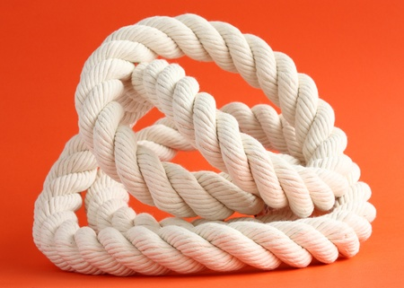 bonding rope: Close-up of a twisted whte cable on red background