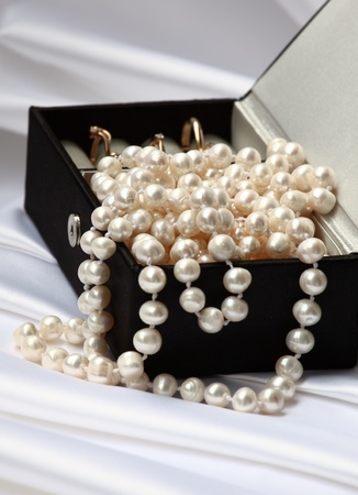 Pearls and gold rings in black jewelry box on neutral background photo